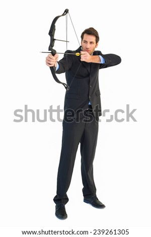 Concentrated handsome businessman practicing archery on white background - stock photo