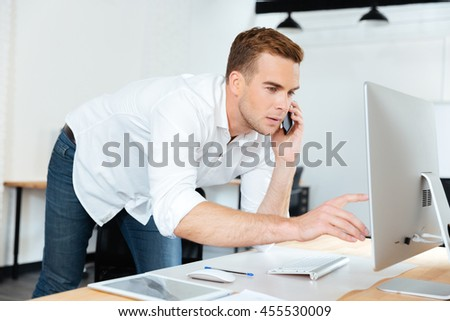 Concentrated handsome businessman talking on mobile phone and using computer in office