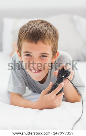 Concentrated little boy lying on bed playing video games at home