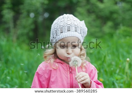 Concentrated little girl blowing on white dandelion seeds pod - stock photo