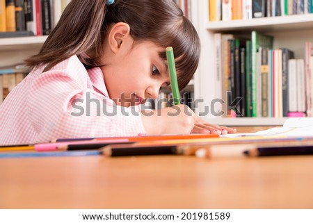Concentrated little girl in uniform doing homework. - stock photo