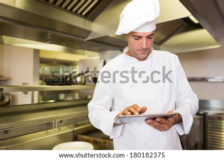 Concentrated male cook using digital tablet in the kitchen - stock photo