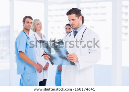 Concentrated male doctor examining x-ray with colleagues standing behind in a medical office - stock photo