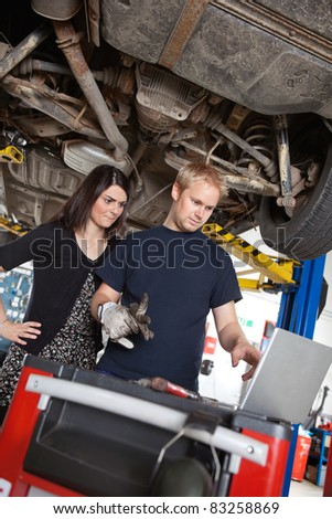 Concentrated man and woman looking at laptop while standing in garage - stock photo