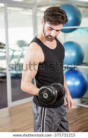Concentrated man lifting dumbbells in the studio - stock photo