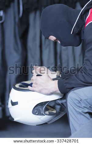concentrated man sitting on the locker room holding his helmet before starting a race in an outdoor go karting circuit - focus on the eye - stock photo