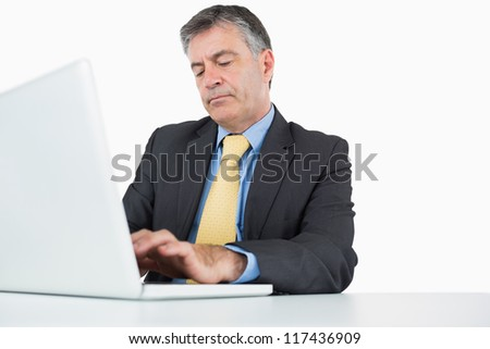Concentrated man typing on his laptop at his desk