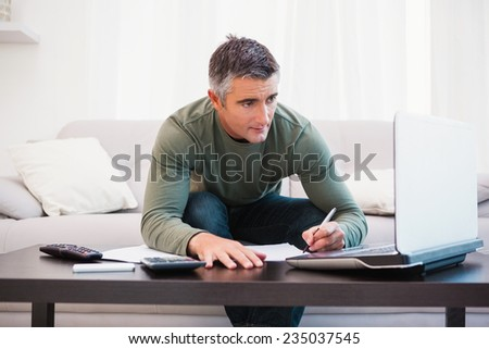 Concentrated man using laptop and taking notes at home in the living room - stock photo