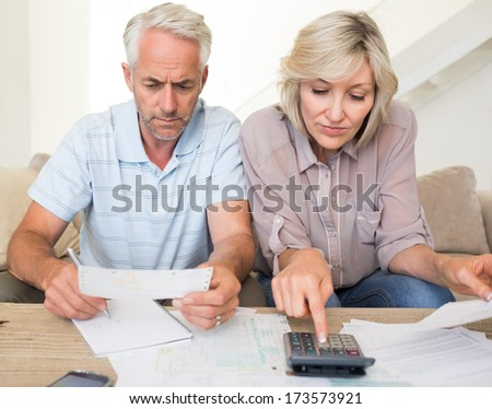 Concentrated mature man and woman with bills and calculator sitting on sofa at home - stock photo