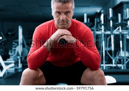 Concentrated mature man looking at camera at gym - stock photo