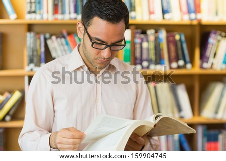 Concentrated mature student reading book against bookshelf in the library