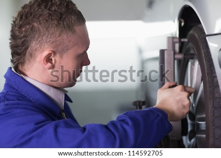 Concentrated mechanic changing a car wheel in a garage