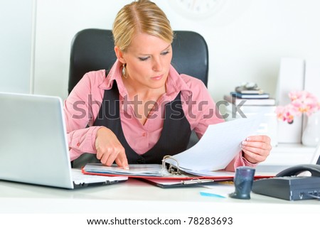 Concentrated modern business woman sitting at office desk and working with financial documents - stock photo