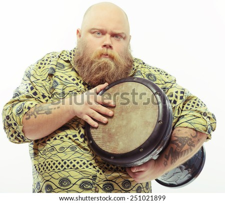 Concentrated on music. Closeup image of funny bearded man with serious face expression holding African drums while standing isolated over white background - stock photo