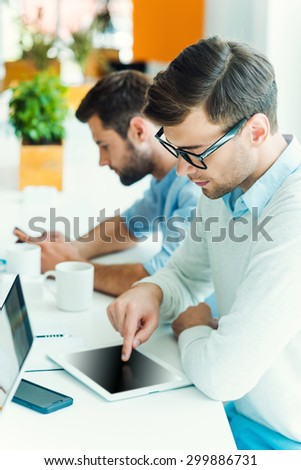 Concentrated on work. Concentrated young man working on digital tablet while his colleague holding mobile phone in the background - stock photo