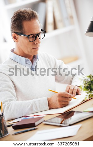 Concentrated on work. Confident mature man writing something in his notebook while sitting at his working place - stock photo