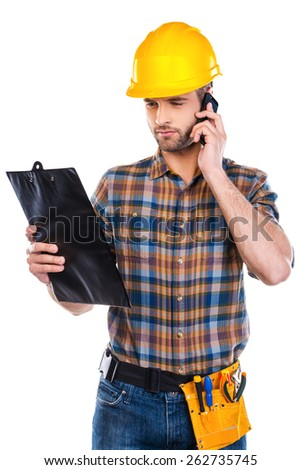 Concentrated on work. Confident young male carpenter in hardhat talking on mobile phone and looking at his clipboard while standing against white background  - stock photo