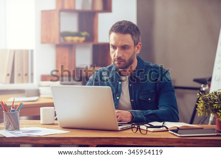 Concentrated on work. Confident young man working on laptop while sitting at his working place in office - stock photo