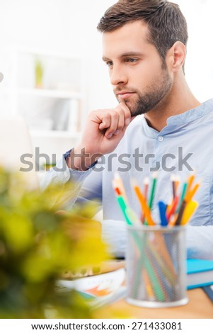 Concentrated on work. Handsome young man in shirt working on laptop and holding hand on chin while sitting at his working place - stock photo