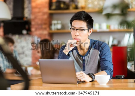 Concentrated pensive young handsome asian man in glasses sitting in cafe, thinking and using laptop - stock photo