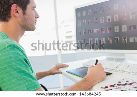 Concentrated photo editor working on graphics tablet at his desk - stock photo