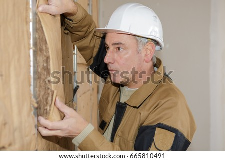 concentrated plasterer worker at a indoors wall insulation works