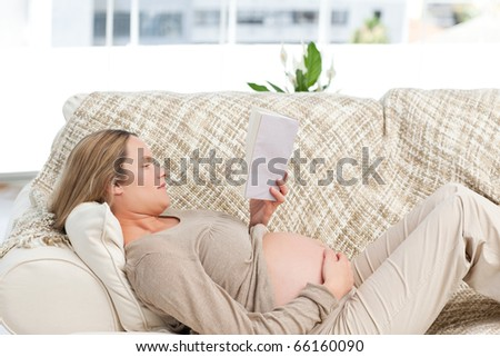 Concentrated pregnant woman reading a book lying on the couch at home - stock photo