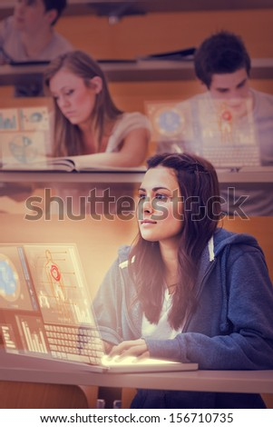 Concentrated pretty student working on her futuristic laptop in lecture hall - stock photo