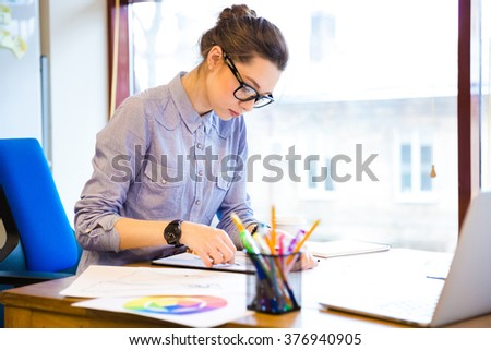Concentrated pretty young woman fashion designer sitting and drawing sketches in office - stock photo