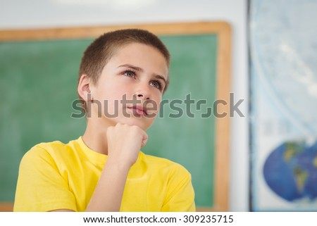 Concentrated pupil having hand on chin in a classroom in school - stock photo