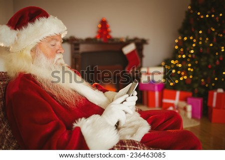 Concentrated santa using smartphone at christmas at home in the living room - stock photo
