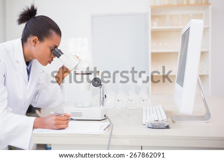 Concentrated scientist looking in microscope in laboratory - stock photo