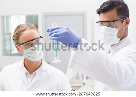Concentrated scientists looking at beaker in laboratory