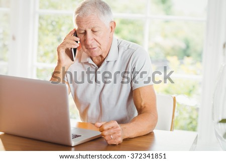 Concentrated senior man looking at laptop and phone calling at home - stock photo
