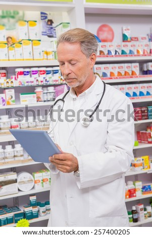 Concentrated senior pharmacist using tablet in the pharmacy