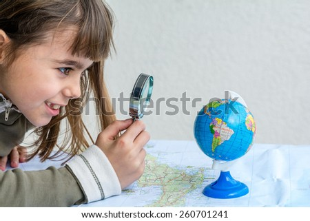 Concentrated seven year old girl examining the map and the globe with a magnifying glass - stock photo