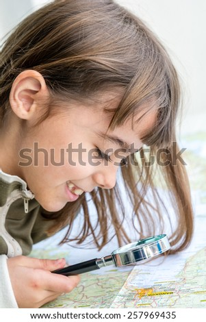 Concentrated seven year old girl is examining the map with a magnifying glass - stock photo