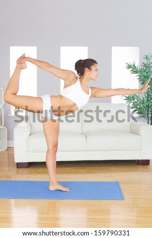 Concentrated slim woman stretching her body in yoga pose on exercise mat in her living room - stock photo