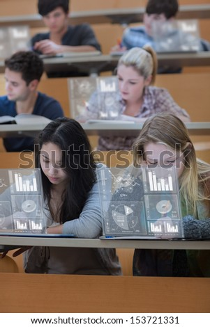 Concentrated students working on their digital tools in lecture hall - stock photo