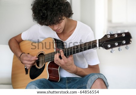 Concentrated teenage musician: closeup of a young musician playing acoustic guitar. Selective focus. - stock photo