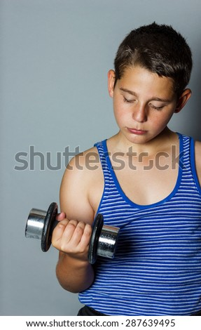 concentrated teenager boy lifting dumb bell - stock photo
