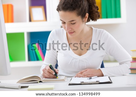 concentrated teenager student doing homework, mark the important data - stock photo