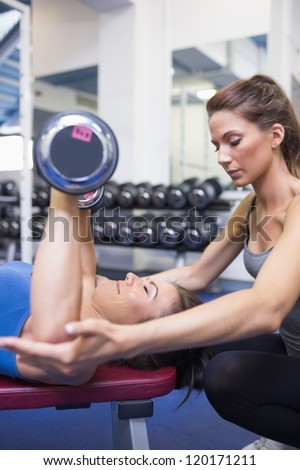 Concentrated trainer teaching woman lifting weights in gym - stock photo