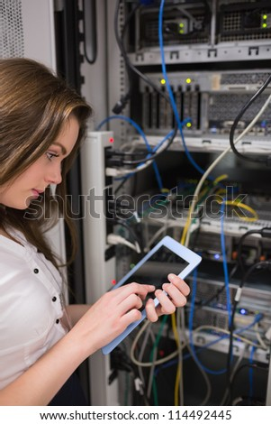 Concentrated woman doing data storage with a tablet pc
