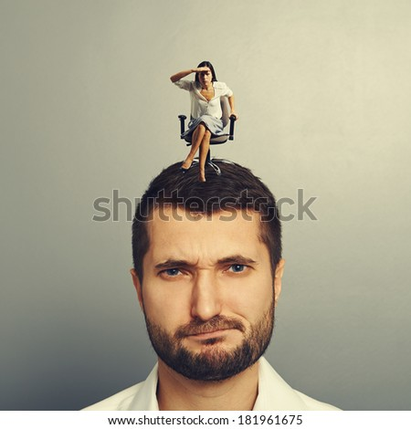 concentrated woman siting on the dissatisfied man and looking into the distance - stock photo