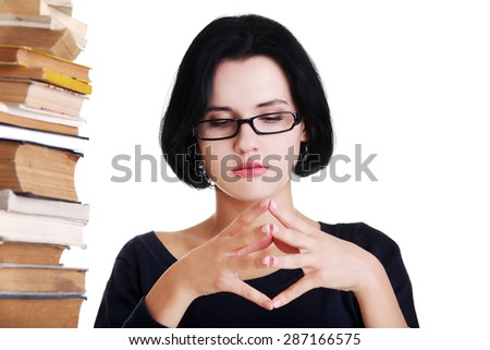Concentrated woman sitting with stack of books. - stock photo