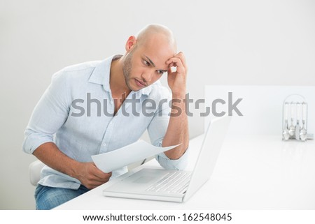 Concentrated worried casual young man using laptop at home - stock photo