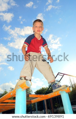 concentrated 7 year old boy standing on monkey bars - stock photo