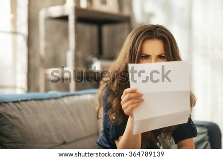 Concentrated young brunet female is sitting on couch and attentively reading letter in loft apartment - stock photo