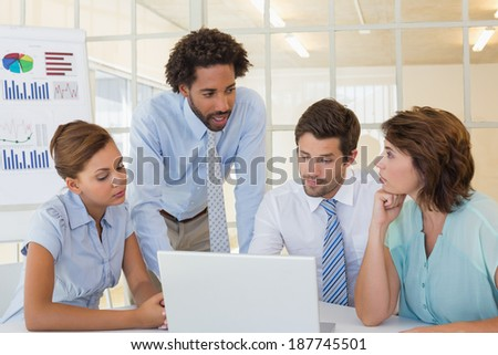 Concentrated young business people using laptop in meeting at office desk - stock photo